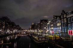 Famous vintage buildings of Amsterdam city at night time. General landscape view at tradition Dutch arcitecture. Stock Photo