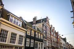 Famous vintage buildings of Amsterdam city at sun set. General landscape view at tradition Dutch architecture. Royalty Free Stock Image