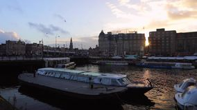 Famous vintage buildings & chanels of Amsterdam city at sun set. General landscape view. Slow Motion Video. AMSTERDAM, NETHERLANDS - JANUARY 10, 2017: Famous stock footage