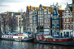 Famous vintage buildings & channels of Amsterdam city at sun set. General landscape view. Royalty Free Stock Photography
