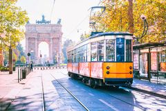 Famous vintage tram in Milan, Lombardia, Italy. Famous vintage tram in the centre of the Old Town of Milan in the sunny day, Lombardia, Italy. Arch of Peace, or Stock Photos