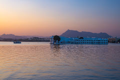 The famous white palace floating on Lake Pichola at sunset. Udaipur, travel destination and tourist attraction in Rajasthan, India.  royalty free stock photography