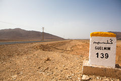 Famous white and yellow road sign, Morocco. Guelmin 139 kilometres - road sign distance indicator on the road to Guelmin with blurred background, Morocco royalty free stock images