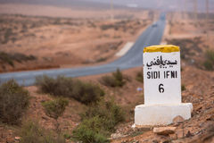 Famous white and yellow road sign, Morocco. Sidi Ifini 6 kilometres - road sign distance indicator on the road to Sidi Ifini with the road in the background royalty free stock image