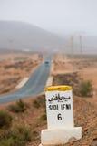 Famous white and yellow road sign, Morocco. Sidi Ifini 6 kilometres - road sign distance indicator on the road to Sidi Ifini with the road in the background stock photo