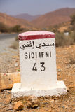 Famous white and yellow road sign, Morocco. Sidi Ifini 43 kilometres - road sign distance indicator on the road to Sidi Ifini with blurred background, Morocco stock photos