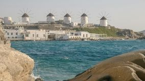The famous windmills on mykonos framed by a rocky shoreline. The famous windmills on the greek island of mykonos framed by a rocky shoreline royalty free stock photo