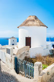 Famous windmills in Oia town on Santorini island, Greece. Stock Photos