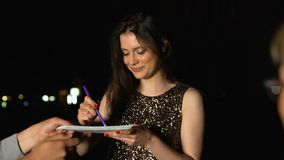 Famous woman signing autographs in fans notebooks at evening party, stars life. Stock footage stock footage
