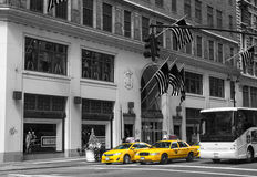Famous yellow-coloured taxi cabs in monochrome b&w passing by in New York City Royalty Free Stock Images