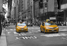 Famous yellow-coloured taxi cabs in monochrome b&w passing by in New York City Stock Photos