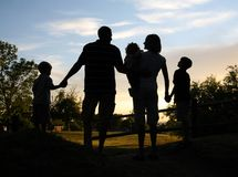 FamSilhouette. Young family silhouetted against sunset Stock Images