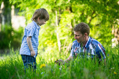 Famyil. Father playing with his small child in the grass. Royalty Free Stock Photography