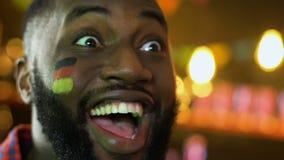 Fanático del fútbol afroamericano que disfruta la victoria preferida del equipo, bandera alemana en mejilla metrajes