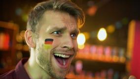 Fanático del fútbol alemán alegre con la bandera en la mejilla feliz para la meta que anota del equipo, triunfo almacen de video