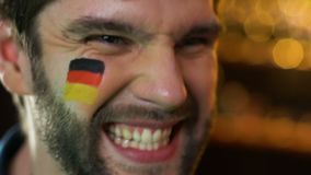 Fanático del fútbol alemán extremadamente feliz sobre la victoria preferida del equipo, bandera en mejilla almacen de video