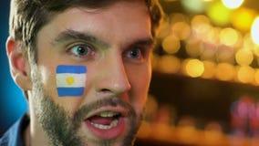 Fanático del fútbol argentino con la bandera en mejilla que disfruta la victoria preferida del equipo almacen de metraje de vídeo