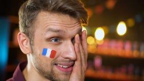 Fanático del fútbol barbudo trastornado con la bandera francesa en la mejilla que hace perder del equipo del facepalm almacen de video