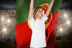 Fanático del fútbol bonito en blanco que anima sosteniendo la bandera de Portugal Fotografía de archivo libre de regalías