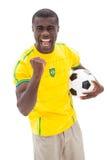 Fanático del fútbol brasileño emocionado que anima sosteniendo la bola Fotos de archivo