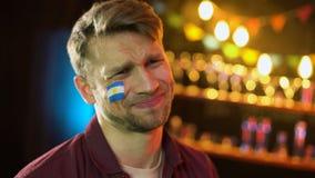 Fanático del fútbol con la bandera argentina en la mejilla que hace el facepalm, infeliz con pérdida almacen de video