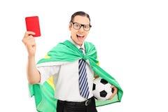 Fanático del fútbol con la bandera brasileña que muestra la tarjeta roja Imágenes de archivo libres de regalías