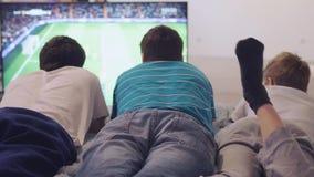 Fanático del fútbol concentrado que mira un partido de fútbol en la TV que miente en el sofá en casa 3840x2160 metrajes