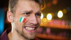 Fanático del fútbol decepcionado con la bandera italiana en la mejilla que hace el facepalm, fracaso metrajes