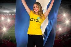 Fanático del fútbol emocionado en la camiseta del Brasil que sostiene la bandera de Honduras Fotos de archivo libres de regalías