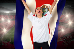 Fanático del fútbol en blanco que anima sosteniendo la bandera de Costa Rica Foto de archivo libre de regalías