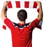 Fanático del fútbol en bufanda que se sostiene roja Fotos de archivo libres de regalías