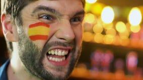 Fanático del fútbol español con la bandera en mejilla que disfruta la victoria preferida del equipo, liga metrajes