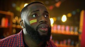 Fanático del fútbol español negro con la bandera en la mejilla decepcionada, equipo nacional que pierde metrajes