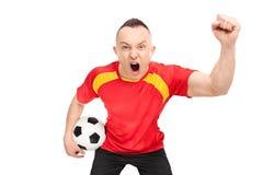 Fanático del fútbol extático que lleva a cabo un fútbol y animar Imagen de archivo libre de regalías