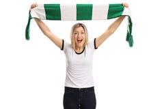 Fanático del fútbol femenino encantado que lleva a cabo una bufanda y animar Imágenes de archivo libres de regalías