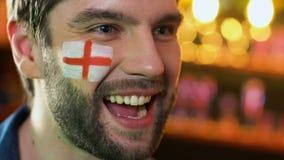 Fanático del fútbol inglés extremadamente feliz sobre la victoria preferida del equipo, bandera en mejilla almacen de metraje de vídeo