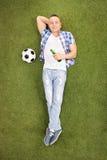 Fanático del fútbol joven que miente en hierba y cerveza de consumición Fotografía de archivo