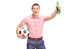 Fanático del fútbol joven que sostiene una botella de cerveza Imagen de archivo libre de regalías