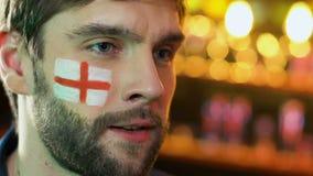 Fanático del fútbol masculino con la bandera inglesa en trastorno de la mejilla sobre pérdida preferida del equipo almacen de metraje de vídeo