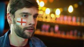 Fanático del fútbol masculino descontentado con la bandera inglesa en la mejilla que hace gesto del facepalm almacen de metraje de vídeo