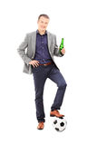 Fanático del fútbol masculino joven que sostiene una cerveza Foto de archivo