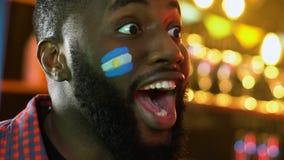 Fanático del fútbol negro con la bandera argentina que anima para la victoria preferida del equipo metrajes