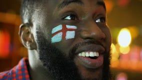 Fanático del fútbol negro con la bandera inglesa que anima para la victoria preferida del equipo, liga almacen de metraje de vídeo