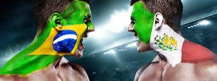 Fanático del fútbol del fútbol o con el bodyart en la cara con la agresión - banderas del Brasil contra México fotografía de archivo libre de regalías