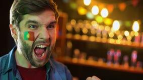 Fanático del fútbol portugués con la bandera en mejilla que anima para el equipo nacional, victoria almacen de video