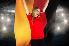 Fanático del fútbol que anima en la bandera roja de Alemania que se sostiene Fotografía de archivo libre de regalías