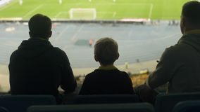 Fanáticos del fútbol ansiosos con el juego de observación del niño en el estadio, frustrado con derrota metrajes