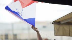 Fanáticos del fútbol ardientes que agitan la bandera del equipo nacional, difusión de observación en la pantalla grande almacen de metraje de vídeo