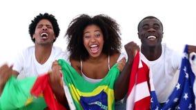 Fanáticos del fútbol en la sentada blanca en el sofá que sostiene banderas almacen de video