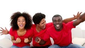 Fanáticos del fútbol en la sentada roja en animar del sofá metrajes